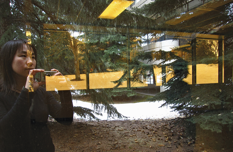 Elsa Lam catches a reflection of herself and the Western Canadian landscape while photographing Craigie Hall at the University of Calgary. Elsa Lam