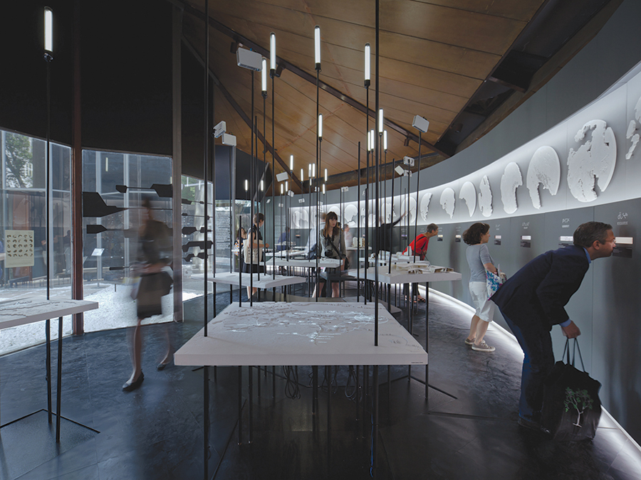 Visitors to Canada's Venice Biennale pavilion peek at photos of Nunavut's 25 communities. Models for imagined future buildings occupy the centre of the space. Latreille Delage Photography
