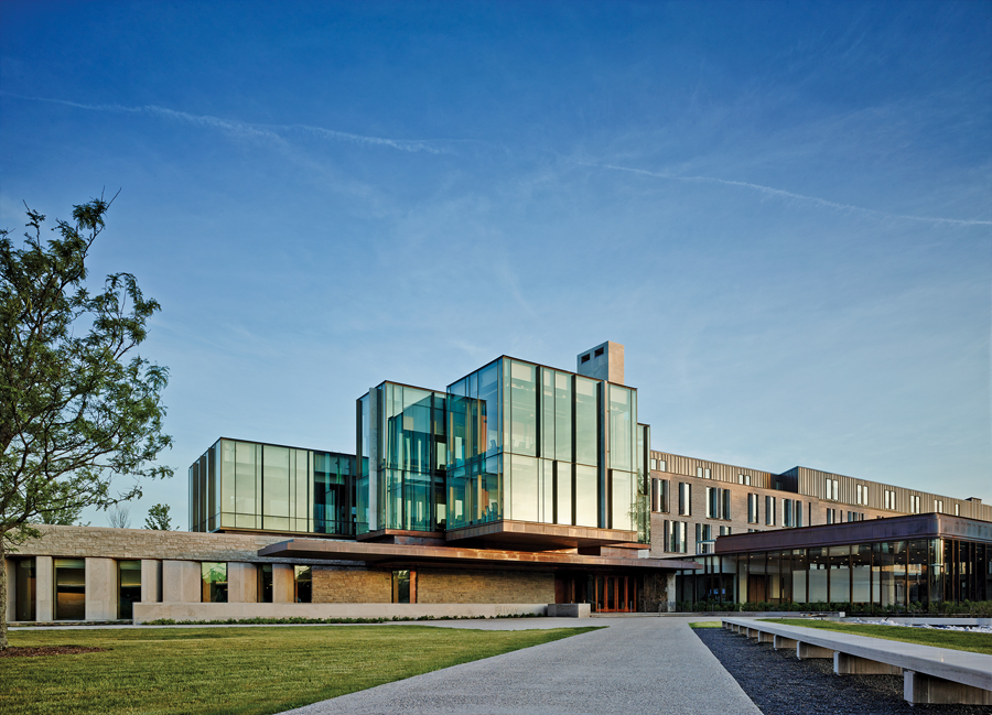 The main entry is topped by a cantilevered glass box containing meeting rooms, and is framed by a sunken auditorium to the left and a formal dining room to the right. Nikolas Koenig