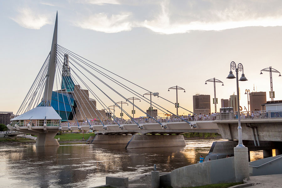 the table for 1200 spans the length of the esplanade riel pedestrian bridge with the canadian museum for human rights visible in the background