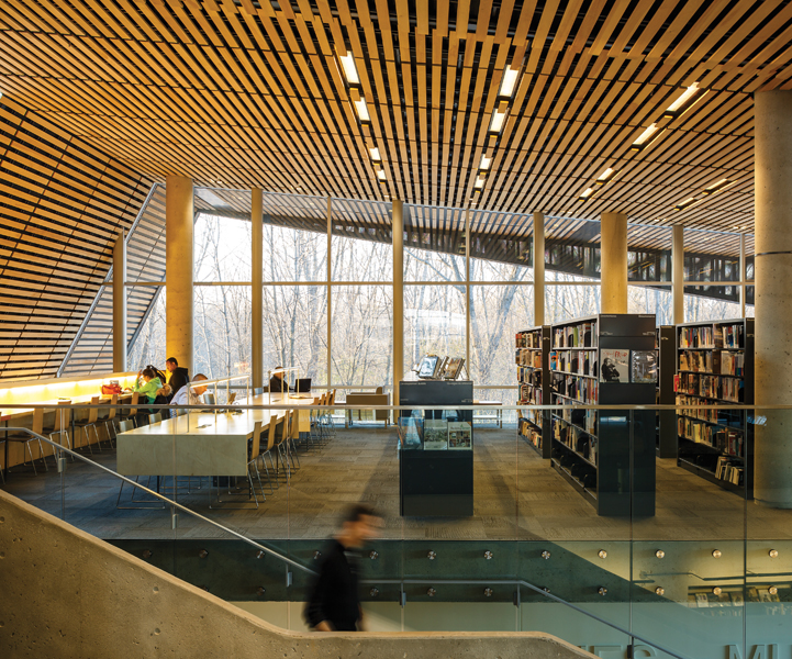 The wood-slat ceiling cantilevers beyond the building envelope, framing vistas of the forest.