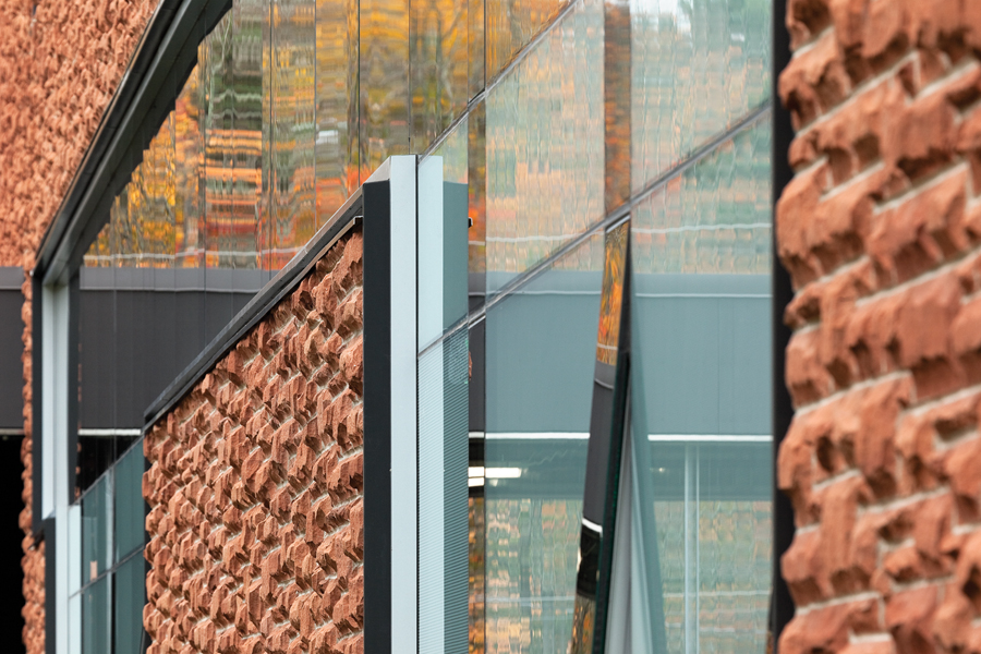 The red sandstone cladding is contained in minimalist black frames.