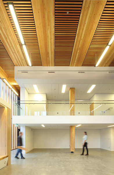 The interior includes exposed glulam columns and ceiling elements made of staggered CLT panels. Photo by Ema Peter
