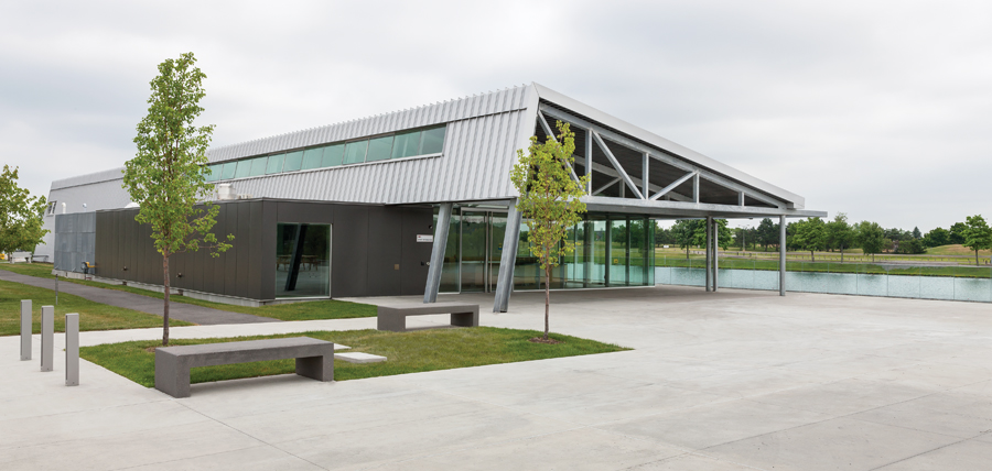 Metal siding wraps from wall to roof of the training facility, accentuating the shed-like structure's modern profile. An open plaza beckons spectators towards the finish-line seating, which cascades down the bank.