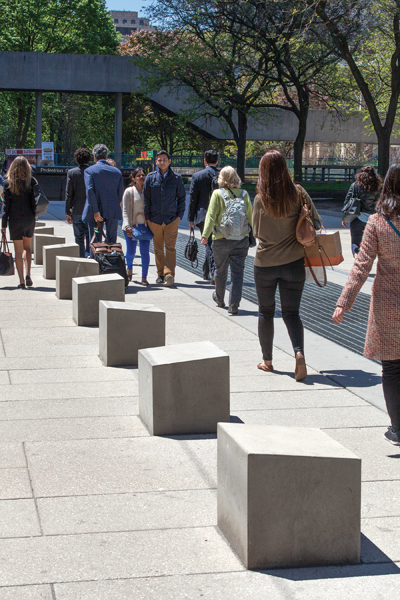 Security bollards double as seating blocks along Queen Street.