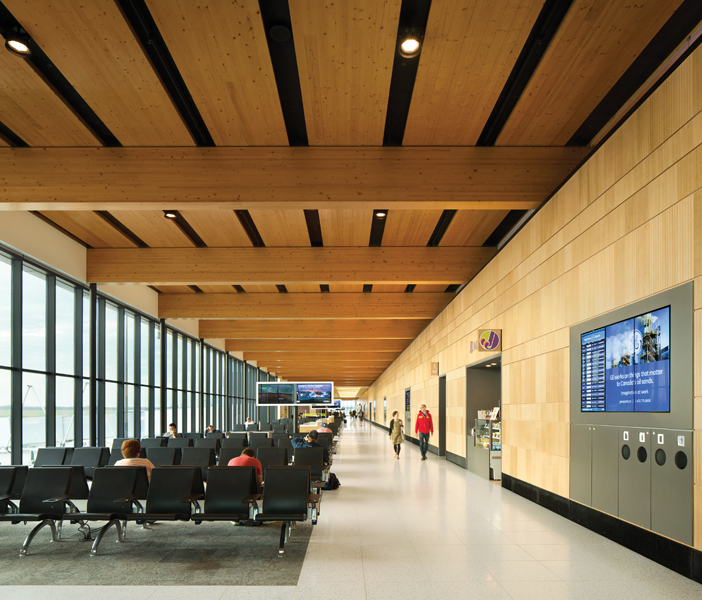 Passengers land and enter into a lounge filled with natural light, enhancing the warmth of the exposed wood ceiling. A wood-clad service wall incorporates information screens, refuse containers and doorways, reducing visual clutter.