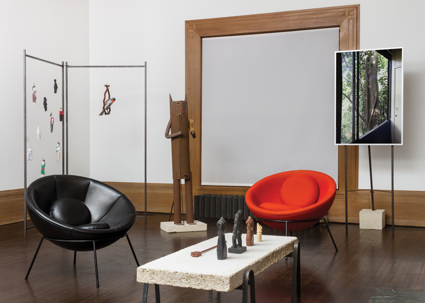 An exhibition room at the Graham Foundation contains photos and artworks by Ioana Marinescu and Madelon Vriesendorp, and two Arper-manufactured Bowl Chairs designed by Bo Bardi in 1951.
