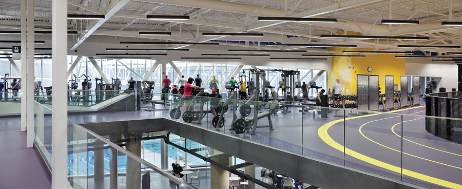The running track intersects an upper-floor fitness area; the elevated track overlooks a lobby between the gymnasium and natatorium. Photo by Tom Arban