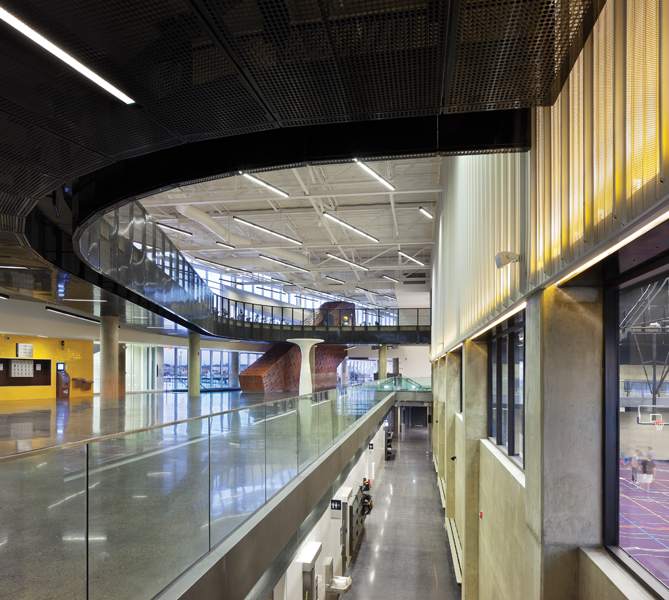 A running track is suspended above a lobby area and circles around the gymnasium, visible at right. Throughout the building, the juxtaposition of many different activities animates the space, giving the centre an urban quality unusual for a suburban facility. Photo by Tom Arban