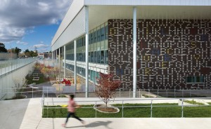 The facility is clad with brown brick embedded with large-scale letters and numbers in white and coloured bricks