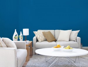 Pairing blue and white in a room with hardwood flooring delivers a coastal, beach-like ambiance. Pictured on the walls of this living area is Blazer Blue by Dulux Paints.
