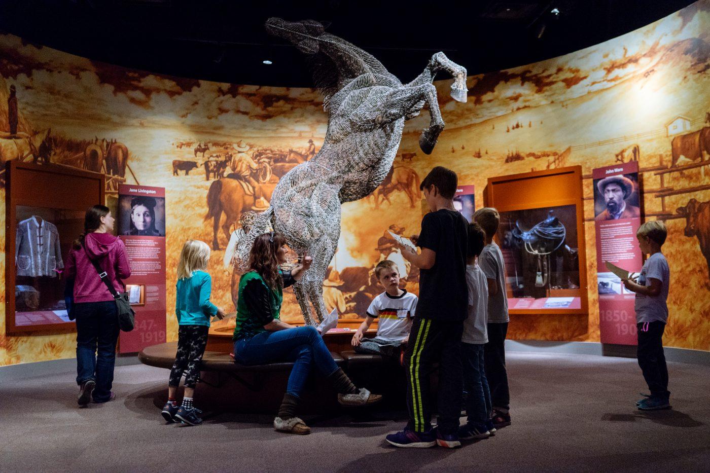 Woman and children gather around horse sculpture