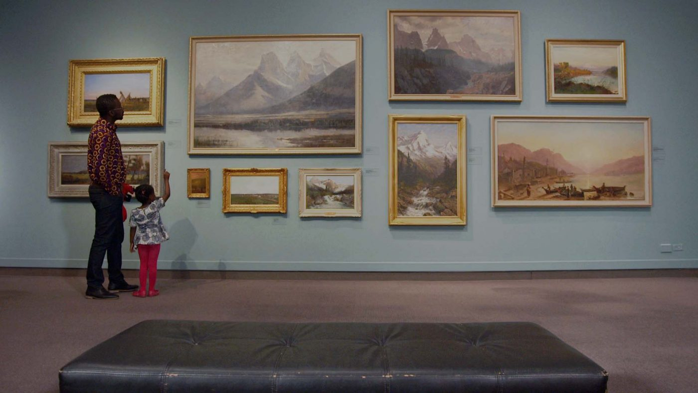 Family looks at framed images in Glenbow gallery
