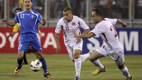 Uzbekistan's Tursunov fights for the ball with Jordan's Zahran and  Al Dmeiri during their 2014 World Cup qualifying match in Amman