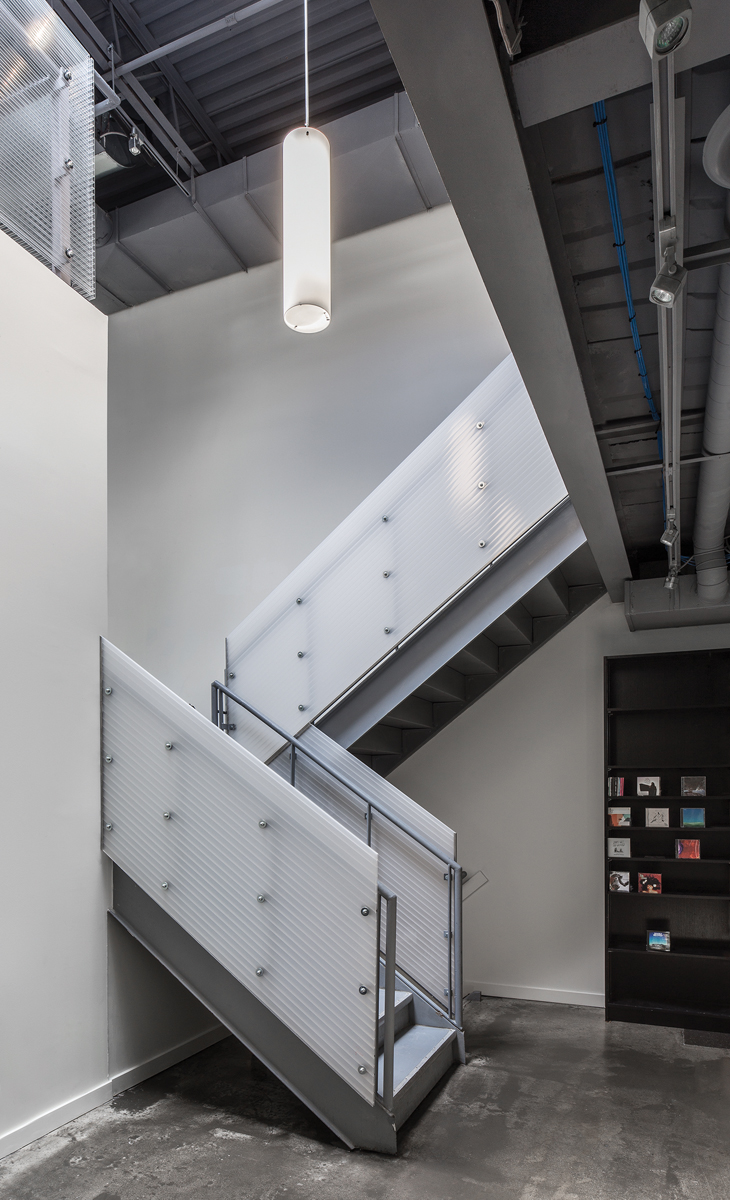 Through the incorporation of skylights, reeded glass and translucent acrylic panels, the interior of this formerly dark warehouse is flooded with natural light. A BetaCalco Cylindra suspended light fixture provides additional illumination. The twin-wall acrylic panels are from Evonik.