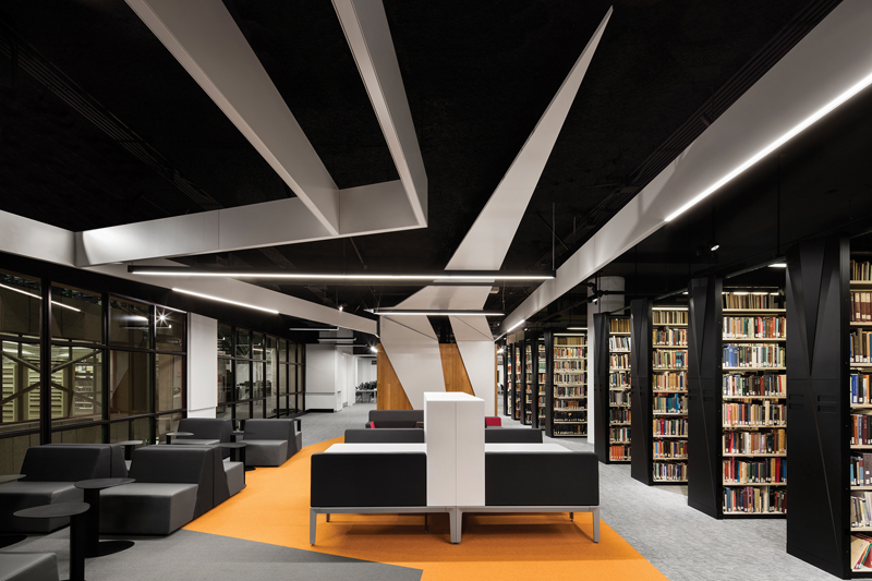 The  pleated  geometry  of  the  ceiling  and  library  shelves,  along  with  the  dynamically  shaped  carpet  inserts,  are  inspired  by  principles  of  anamorphic  design