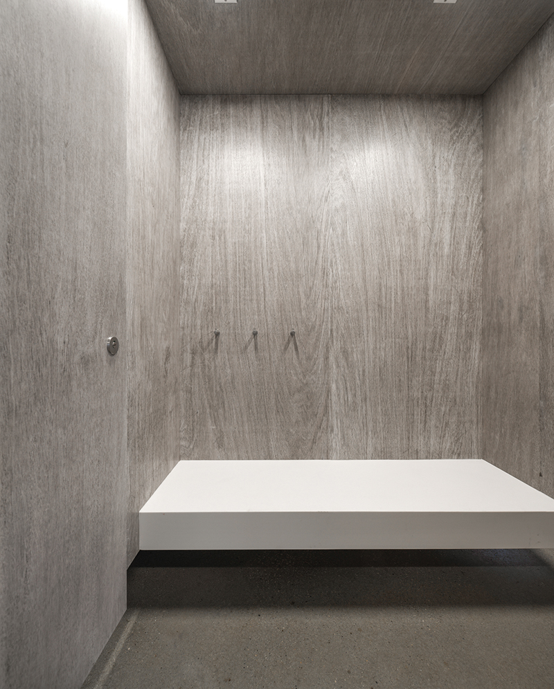 The changeroom walls are made of marine-grade plywood that has been rubbed with black and white paints to bring out the material's natural grain.