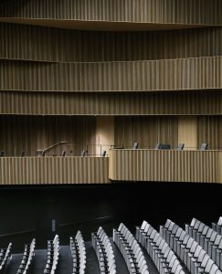 The 860-seat auditorium uses an elegant wood-and-grey palette.
