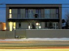 Site planFacing page: undulating walls of glass and wood panels create distinction and modulate the sun and wind at the ends of each unit.Top: an elevation drawing shows the simplicity of the box volume. Above right: a night view of the fourplex.