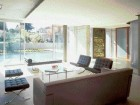 The enclosed front yard with the pond compliments the spatial qualities of the living room containing furniture that reinforces references to the Barcelona Pavilion