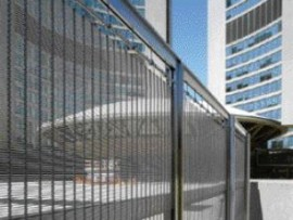 while preventing public access to the podium level at Toronto's City Hall, the interconnected gates preserve transparency through their protective curtain.