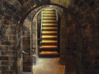 a stairway at the end of a series of low brick archways that once supported heavy vats of spirits stored overhead