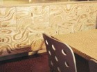 the surface of the plywood has been routered to create a pattern that moves across the panel joints and disregards the limitations of the plywood sheets