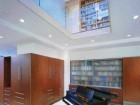 Two-storey atrium permits ample clerestory lighting from above to illuminate the ground floor living room.