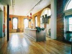 Top Exposed Brick Walls and Burnished Wood Floors Enhance the Grand Ballroom Space on the Hotel's Ground Floor