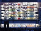Night View Into the West Elevation of the Building Reveals a Stack of Brightly Coloured Planes Enclosing Laboratory Spaces.