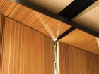 In the Recital Hall, the Texture and Grain of the Wool-Panelled Wall Is Visible as It Wraps Around the Ceiling Plane Beneath the Suspended Acoustic Ceiling Panels.