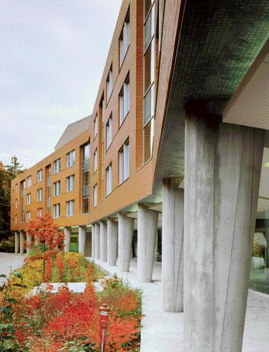 Tapered Concrete Columns Supporting Brick-Clad Residential Clusters Define the Exterior Walkway.