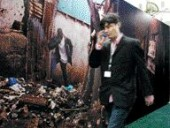 A Delegate Walks Past a United Nations Exhibit on Informal Housing.