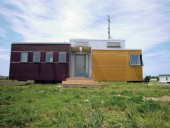 Contrasting Colours and Cladding Material Define the Various Zones of the Minihome, Temporarily Laid to Rest on a Grassy Field.