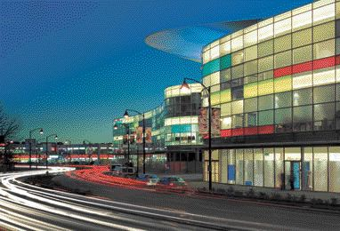 While Showcasing Retail Spaces Contained Within, the Undulating Glass Facade Is Accentuated by the Sporadic Expression of Rainbow-Hued Backlit Glass Panels.
