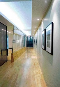 The Gallery Wall of the Polar Capital Office Benefits From Concealed Reflected Ceiling Light, While a Series of Pot Lights Wash Down the Wall to Highlight the Art Pieces Punctuating the Corridor.