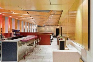 """Interior View of the Restaurant Reveals the """"Buckling"""" Compressed Sapele Wood Ceiling Plane, the Grid of White Ceramic Plates Decorating the Back Wall, and a Bold Colour Scheme of Vibrant High-Gloss Fuchsia and White in Addition to Gold-Toned Satin-Finish Aluminum Sheathing."""