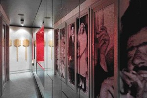 The Washroom Corridor at Il Fornello Is Adorned With Enlarged Black and White Photographs of the Owners' Ancestors, While Long Wooden Pizza Paddles are Exhibited as Decorative Objects Hung in a Series.
