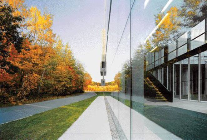 The Building Appears to Dematerialize Against the Trees Due to Its Impossibly Thin Glass Membrane.