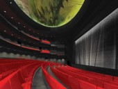 In the interior of the auditorium, the evocative visual effect of ceiling artwork is enhanced by recessed cove uplighting, and is balanced with the contrasting qualities of lush red upholstery and black peripheral surfaces.