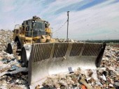 Specially modified bulldozers compact trash