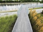 One of the viewing bridges traverses the tall prairie grass plantings in the garden and leads toward the canal walkway, inviting visitors to engage with the landscape on a number of levels.
