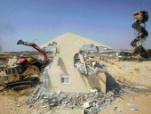 Israeli Defence Forces use Bulldozers to demolish a house in the Jewish settlement of Morag in the southern Gaza Strip.
