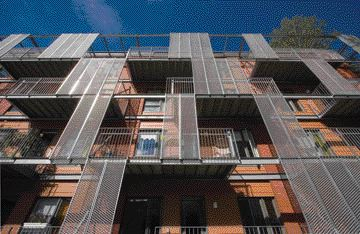 Industrial stair treads made of galvanized metal become privacy screens for the residents' balconies