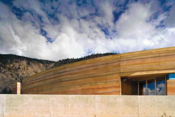 The gently curved rammed-earth wall set against the unusual desert sky of osoyoos in British Columbia's interior.