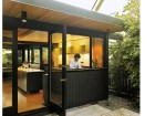 FURTHER INTEGRATING INTERIOR AND EXTERIOR SPACES, A LARGE FULLY GLAZED DOOR SWINGS OPEN FROM THE KITCHEN TO THE PATIO.