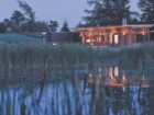 VARIOUS PHOTOS AND DRAWINGS INDICATE THE SITING OF THE HOUSE IN ERIN MILLS AT THE LOWEST POINT OF THE PROPERTY TO CAPTURE VIEWS OF THE ADJACENT MARSH AND ROLLING MEADOW IN THE IMMEDIATE AND MIDDLE GROUND.