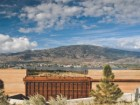 THE COR-TEN STEEL COMPLEMENTS THE WARM TONES OF THE RAMMED-EARTH WALL WHILE LAKE OSOYOOS CAN BE SEEN IN THE DISTANCE.