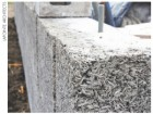 Blocks of Durisol--manufactured from recycled waste wood and filled with 50% slag concrete--are assembled on site.
