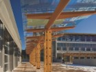 Glass-and-cedar canopies shield students from the elements as they walk across the central courtyard.